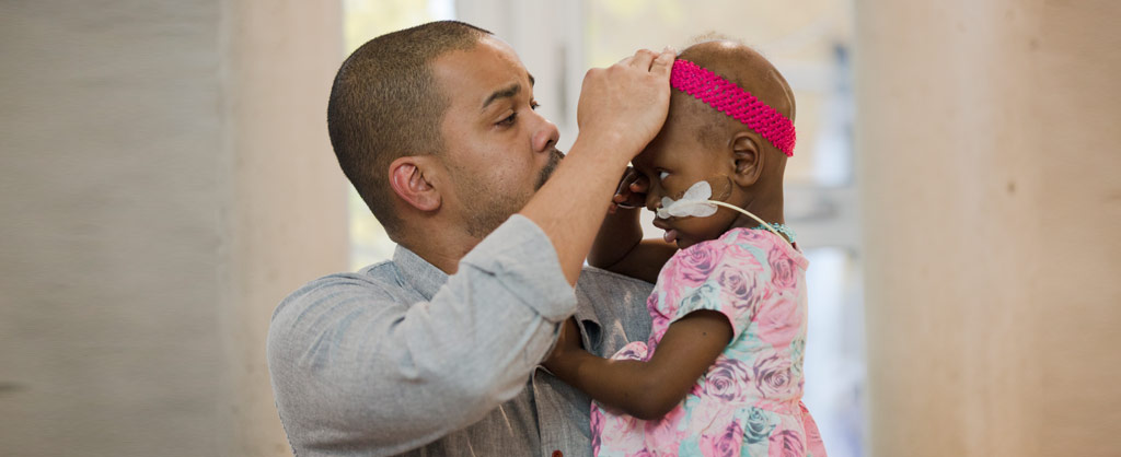 Man holding sick daughter