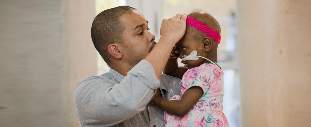 Man holding sick daughter